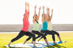 Smiling sporty women doing warrior pose in yoga class Stock Image