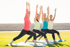 Smiling sporty women doing warrior pose in yoga class Royalty Free Stock Image
