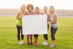 Smiling sporty women holding poster with copy space Royalty Free Stock Image