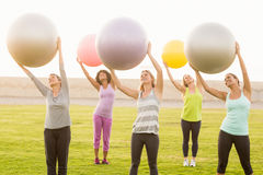 Smiling sporty women working out with exercise balls. In parkland Royalty Free Stock Photography