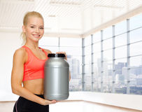 Smiling spory woman holding protein jar Stock Images