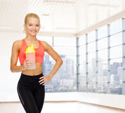 Smiling spory woman with protein shake bottle Stock Images