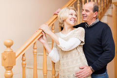 Smiling spouses leaning against stairway Stock Image