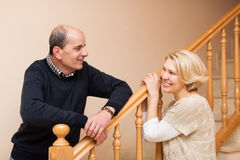 Smiling spouses leaning against stairway Stock Photos