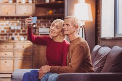 Smiling spouses taking selfies at home royalty free stock photo