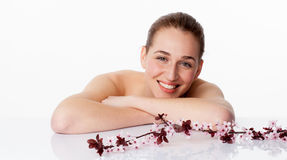 Smiling, spring spa concept. Spring spa concept - thrilled beautiful young woman leaning her face down on white glass for fresh natural skincare on white Royalty Free Stock Images