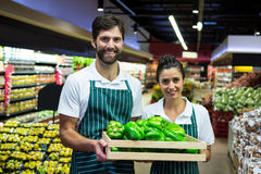 Smiling staff holding a crate of green bell pepper at supermarket Royalty Free Stock Image