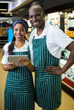 Smiling staff using digital tablet in organic section. Portrait of smiling staff using digital tablet in supermarket Royalty Free Stock Images