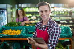 Smiling staff using digital tablet in organic section. Portrait of smiling staff using digital tablet in organic section of supermarket Stock Image
