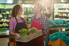 Smiling staffs holding basket of vegetable in organic section. Of supermarket Royalty Free Stock Images