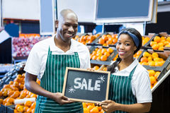 Smiling staffs holding sale sign board in organic section. Portrait of smiling staff holding sale sign board in organic section of supermarket Royalty Free Stock Photos