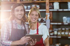 Smiling staffs using digital tablet in organic section. Portrait of smiling staffs using digital tablet in organic section of supermarket Royalty Free Stock Photos