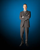 Smiling standing businessman in suit. Isolated on blue Royalty Free Stock Photography