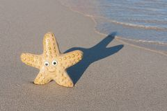 Smiling starfish with victory sign on the beach Royalty Free Stock Images