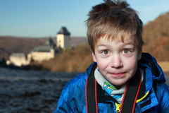 Smiling and staring boy with the camera belt by the castle Royalty Free Stock Photo