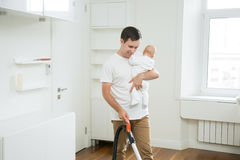 Smiling stay-at-home dad vacuum cleaning the carpet holding a ba Royalty Free Stock Images