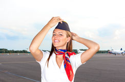Smiling stewardess on the airfield. With planes on background Stock Images