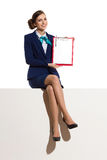 Smiling Stewardess Sitting On A Top And Showing Clipboard. Elegant woman in blue suit and black high heels is sitting on a top with legs crossed, presenting Royalty Free Stock Photos