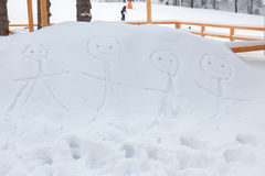 Smiling stickman family drawn by hand in snow Royalty Free Stock Photography