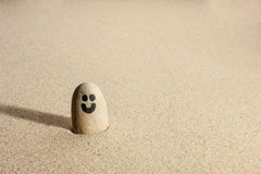 Smiling stone sticking out of the sand Royalty Free Stock Photos