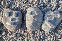 Smiling stones. Three smiling faces stones in the beach Stock Photos