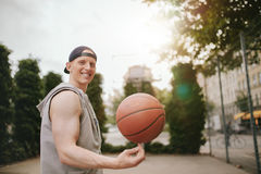Smiling streetball player spinning the ball. Portrait of smiling streetball player spinning the ball on outdoor court. Happy young man balancing basketball on Stock Photos