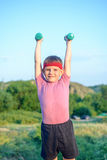Smiling Strong Boy Raising Two Dumbbells Stock Photos