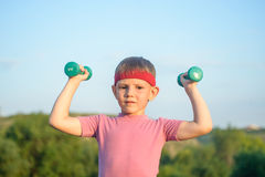 Smiling Strong Boy Raising Two Dumbbells Stock Photography