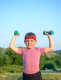 Smiling Strong Boy Raising Two Dumbbells Royalty Free Stock Photos