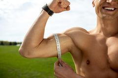 Happy athlete is measuring biceps royalty free stock photo