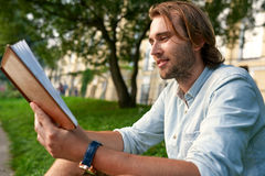 Smiling strubble man holding a book on the grass in the campus. Back to school concept. Smiling stubble man holding a book on the grass in the campus. Back to Royalty Free Stock Photo