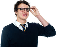 Smiling student adjusting his spectacles Stock Images
