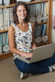Smiling student against bookshelf with laptop on the library floor. Portrait of a smiling female student sitting against bookshelf with laptop on the library Royalty Free Stock Photo