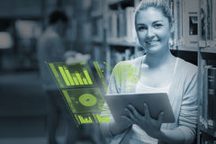 Smiling student analysing figures on her futuristic tablet Royalty Free Stock Photo