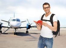 Smiling student with backpack and book at airport Stock Image