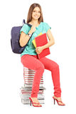 Smiling student with bag holding notebooks and sitting on books Stock Photos