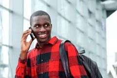 Smiling student with bag talking on phone. Portrait of smiling african student with bag talking on phone Royalty Free Stock Photos
