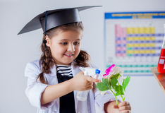 Smiling student biologist sprinkles flower Royalty Free Stock Images