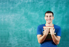 Smiling Student blackboard. Portrait of a smart young man smiling feeling confident happy,in front of a notebook  standing against chalkboard Stock Image