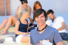 Smiling student boy with friends outside college. Holding books summer Stock Images