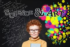 Smiling student boy in glasses with science formulas and art pattern background royalty free stock photos