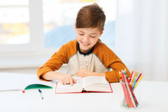 Smiling, student boy reading book at home Royalty Free Stock Images