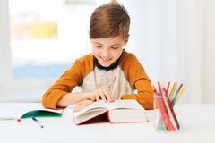 Smiling, student boy reading book at home Royalty Free Stock Photo