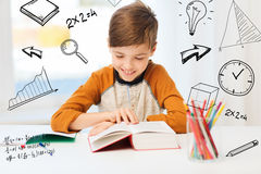 Smiling, student boy reading book at home. Education, childhood, people, homework and school concept - happy student boy reading book or textbook at home over Stock Photo