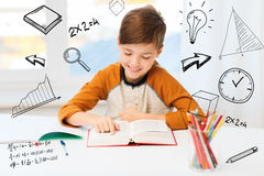 Smiling, student boy reading book at home. Education, childhood, people, homework and school concept - happy student boy reading book or textbook at home over Stock Photos