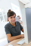 Smiling student boy working on desktop computer Royalty Free Stock Photo