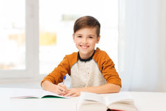 Smiling student boy writing to notebook at home. Education, childhood, people, homework and school concept - smiling student boy with book writing to notebook at Stock Image