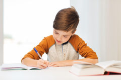 Smiling student boy writing to notebook at home Royalty Free Stock Images