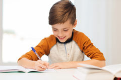Smiling student boy writing to notebook at home Stock Images