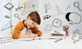 Smiling student boy writing to notebook at home. Education, childhood, people, homework and school concept - smiling student boy with book writing to notebook at Royalty Free Stock Photo